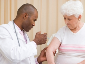 Doctor giving vaccination to woman in exam room