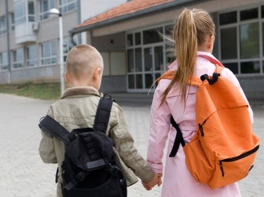 a young boy and girl hold hands while walking to school