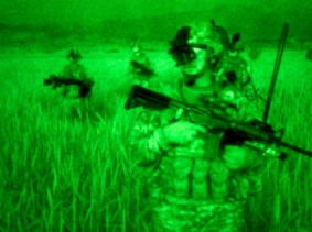 As seen through a night-vision device, U.S. Army soldiers move through grasses to an overwatch position in Afghanistan