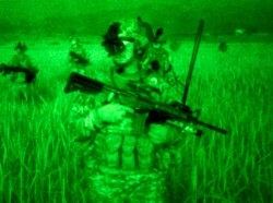 As seen through a night-vision device, U.S. Army soldiers move through grasses to an overwatch position in Sabari, Khowst province, Afghanistan