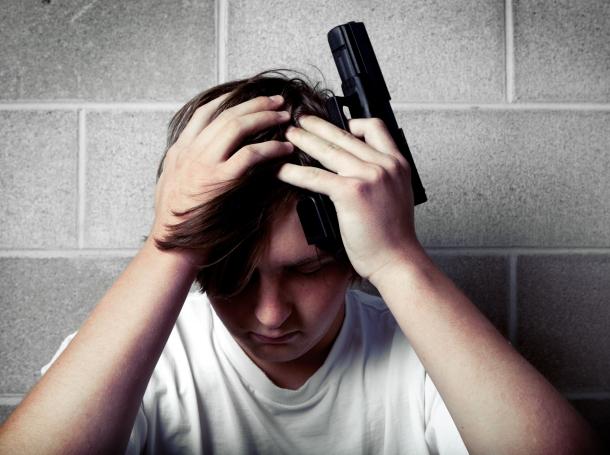 depressed teenage boy with handgun