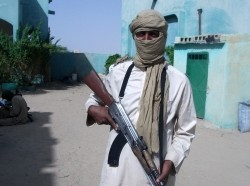 A Tuareg rebel in Mali poses with an assault rifle.