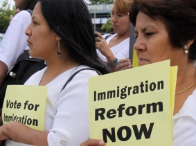 At a rally, two women hold signs calling for immigration reform