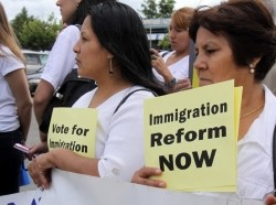 At a rally, two women hold signs calling for immigration reform.