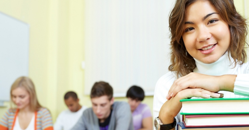 girl in a classroom with a stack of textbooks
