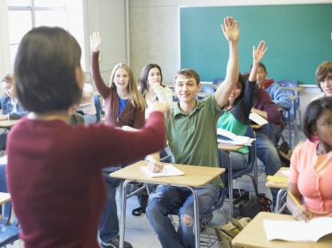 secondary school students raising their hands in class