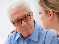 doctor consoling elderly man