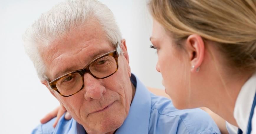 doctor consoling elderly man