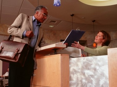 man talking to receptionist at clinic reception
