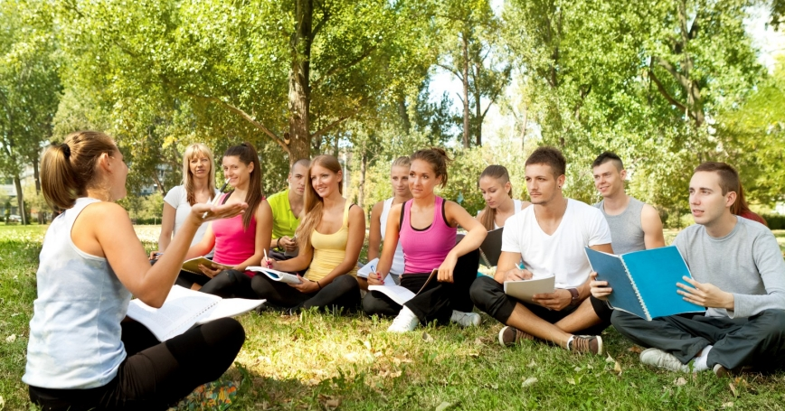 group sitting on grass with a discussion leader