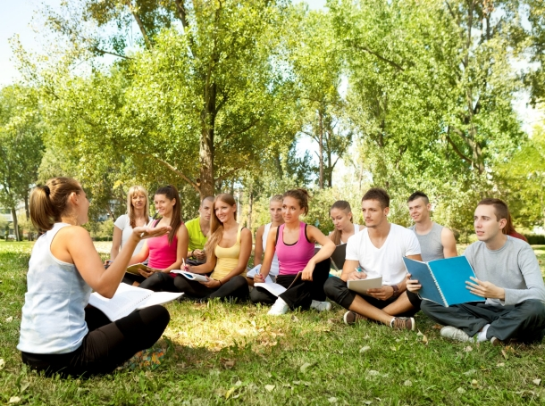 a group sitting outside with a teacher leading discussion