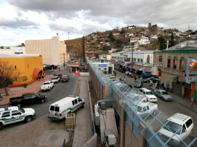 The towns of Nogales, Ariz., left, and Nogales, Mexico, stand separated by a high concrete and steel fence