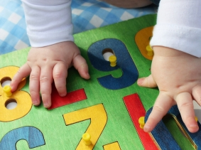a child's hands on a number puzzle