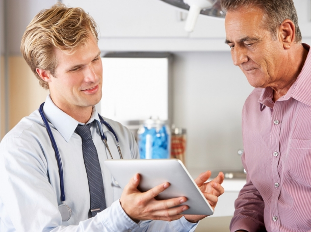 doctor showing a tablet to a patient