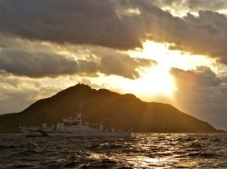 A Japanese Coast Guard patrol vessel passes by Uotsuri, the largest island in the Senkaku/Diaoyu chain