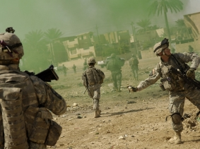 U.S. Army sergeant throws a smoke grenade to mask his team's movements during a joint operation with the Iraqi police