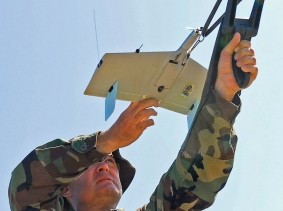 A sailor prepares to launch a small Unmanned Aerial Vehicle (UAV)