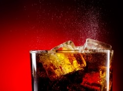 a glass of cola with ice cubes