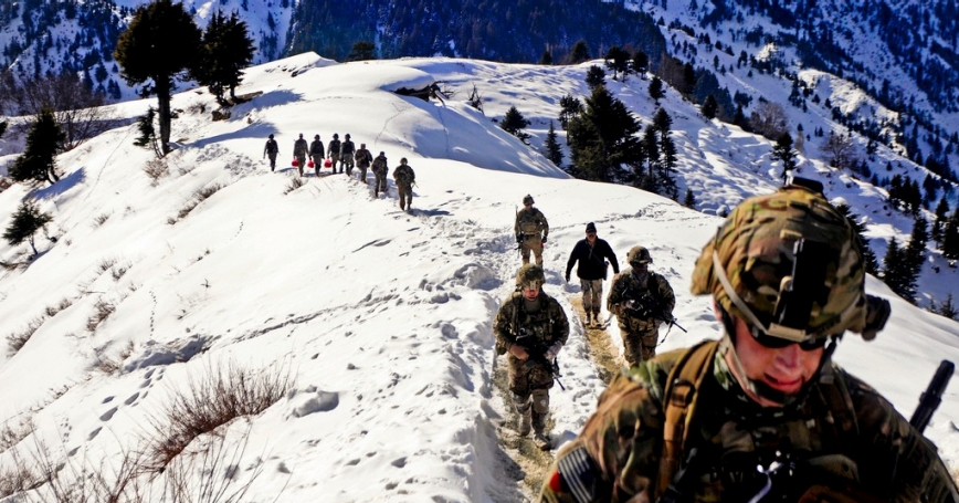 Afghan Border Police and U.S. Army Soldiers hike to an observation point along the Afghanistan-Pakistan border