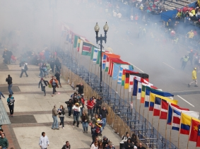 A cloud of smoke envelopes the street after a bomb explodes at the Boston Marathon