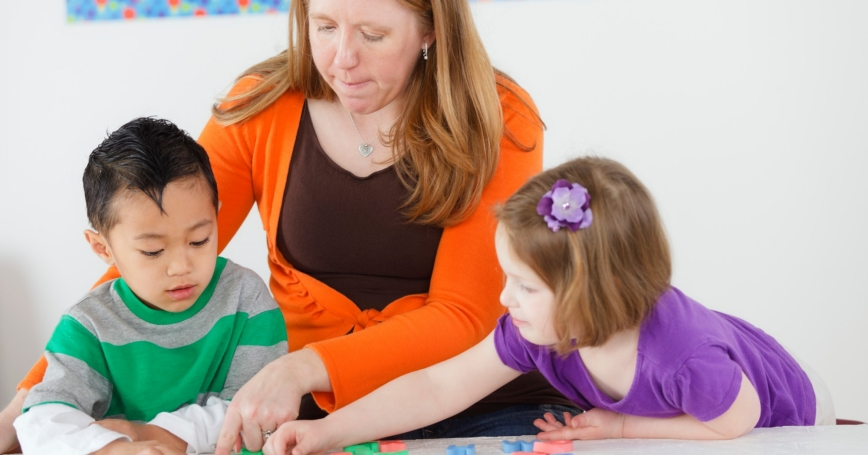 preschool children using letters with their teacher