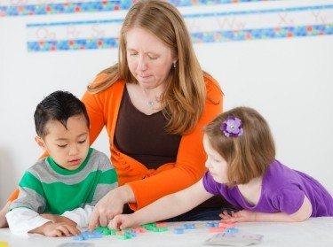 Preschool children using letters with a teacher