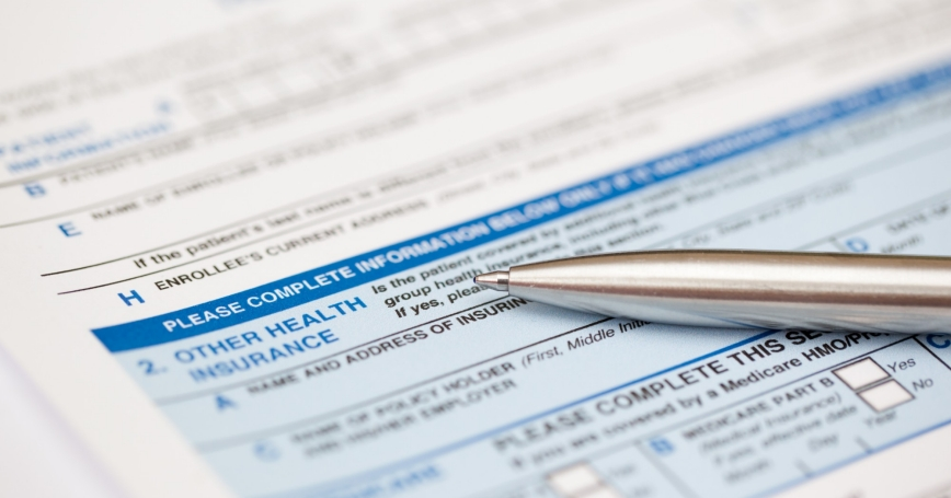a health insurance form and a pen