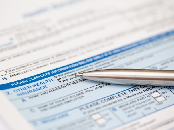 a health insurance claim form and a silver pen