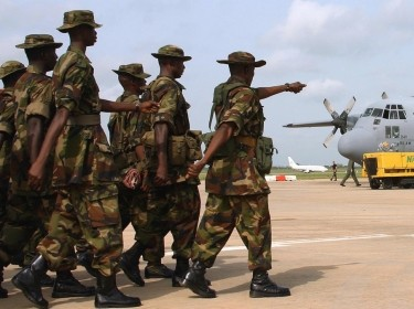 Nigerian troops march toward an Air Force C-130 Hercules
