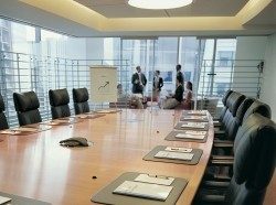 Group of people discussing a business plan in a distant office with a conference table in the foreground