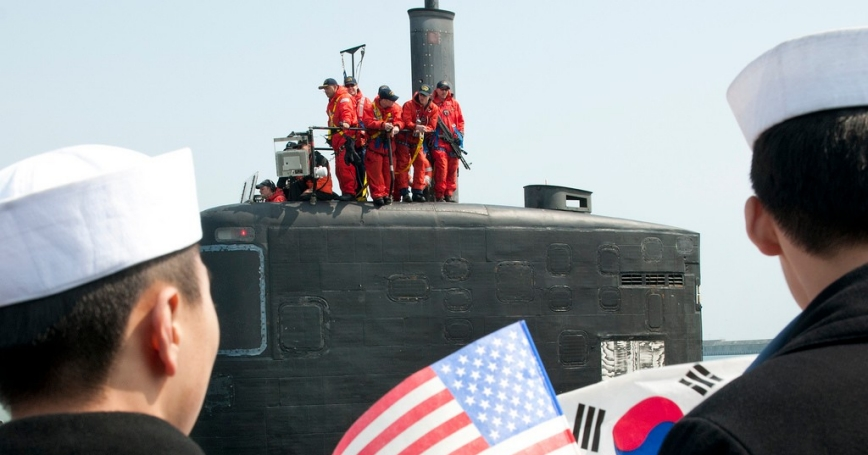ROK Navy sailors wave U.S. and ROK flags to welcome Los Angeles-class submarine USS Cheyenne to Busan