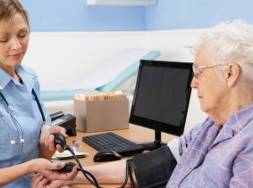 UK nurse taking a woman's blood pressure