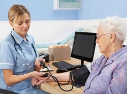 UK nurse taking a woman's blood pressure