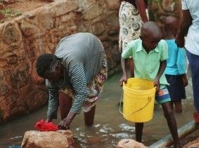 Women and children collecting water from the unimproved water source of Asengo Community. Asengo Community, Kisumu, Kenya