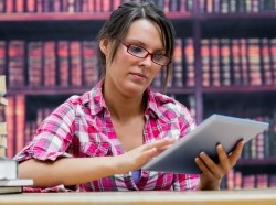 woman in a library using a tablet computer