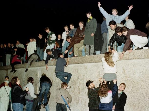 East German citizens climb the Berlin wall at the Brandenburg Gate as they celebrate the opening of the border November 10, 1989