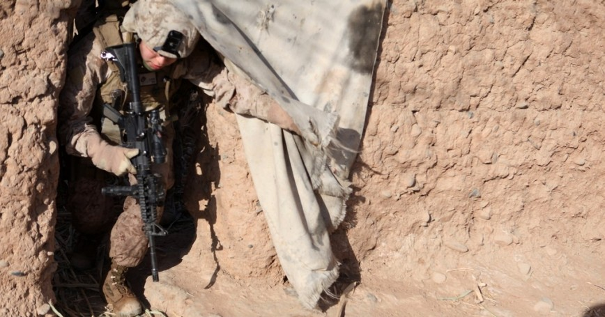U.S. Marine Corps 1st Lt., a female engagement team commanding officer, crawls through a doorway during a patrol in Marjah, Helmand province, Afghanistan