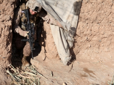 a female engagement team (FET) commanding officer, crawls through a doorway during a patrol in Marjah, Helmand province, Afghanistan