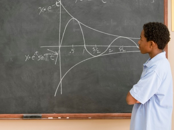 high school student looking at graph on blackboard