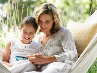 A mother and daughter read a book while sitting in a hammock