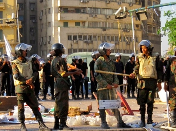Egyptian police stand talking to each other, the visors on their riot helmets raised.