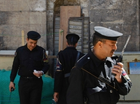 Egyptian policemen on guard by the entrance to the Ayyubid 13th century Madrasa of al-Salih Ayyub in Cairo, Egypt