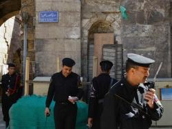 Egyptian policemen on guard by the entrance to the Ayyubid 13th century Madrasa of al-Salih Ayyub in Cairo, Egypt