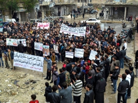 Crowd of Syrians standing amid destruction
