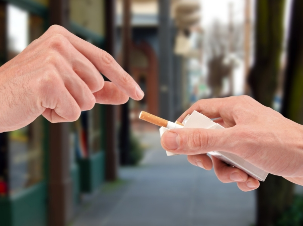 offering a cigarette from the pack on the street
