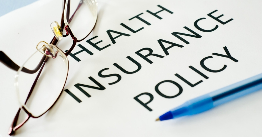 health insurance policy and reading glasses