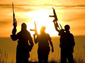 Soldiers with rifles stand in front of a sunset.