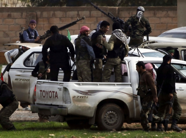 Members of the Free Syrian Army gather as gunfire is heard between them and the armed Kurds of the Kurdish Democratic Union Party (PYD) in the northern Syrian town of Ras al-Ain, Nov. 25, 2012.