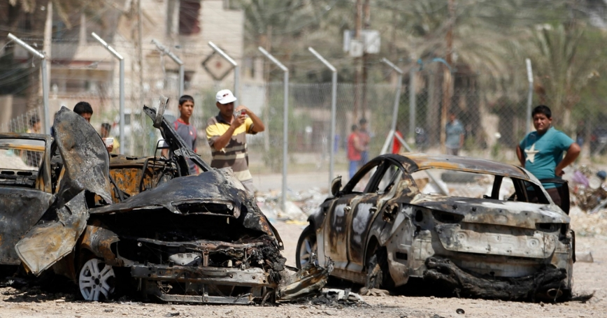 People gather at the site of a car bomb attack in Baghdad August 15, 2013