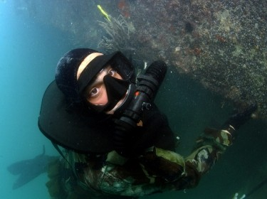 A U.S. Navy SEAL hangs on to a pier during a combat swimmer training dive